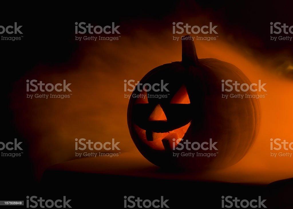 A scary Halloween pumpkin in smoke  stock photo