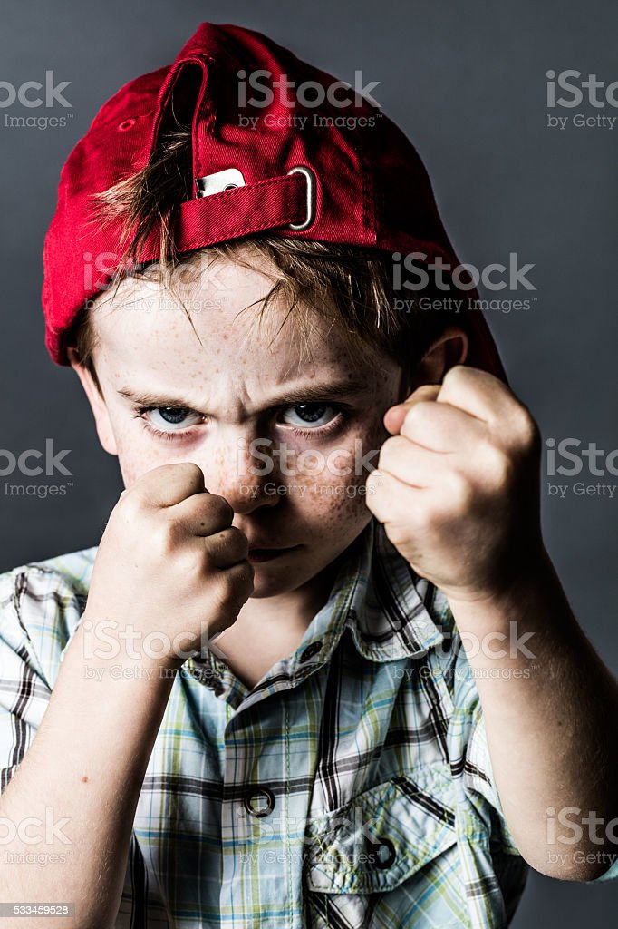 scary kid with freckles and hat back boxing and bullying stock photo
