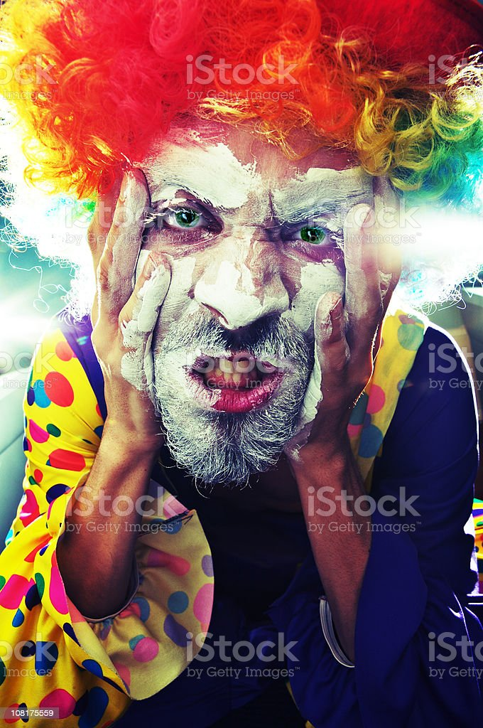 Scary Man in Clown Costume Applying Face Paint stock photo
