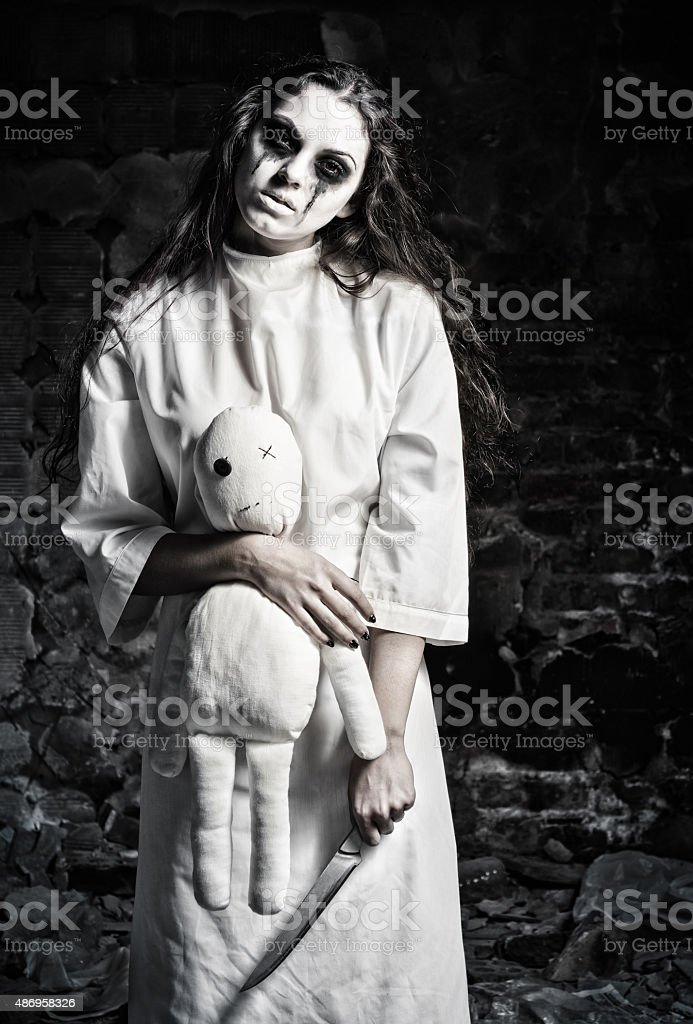 Scary monster girl with moppet doll and knife in hands stock photo