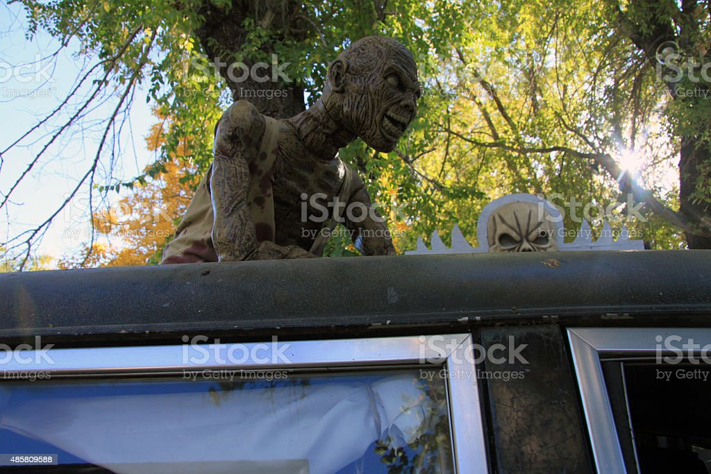 Scary monster on top of hearse stock photo