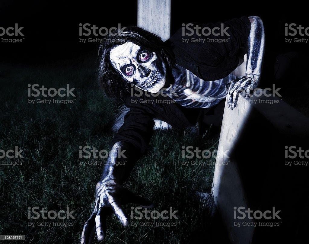Scary Skeleton Crawling on Ground at Night stock photo