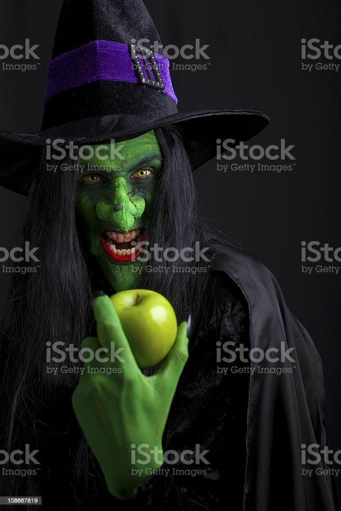 Scary witch holding an apple. royalty-free stock photo