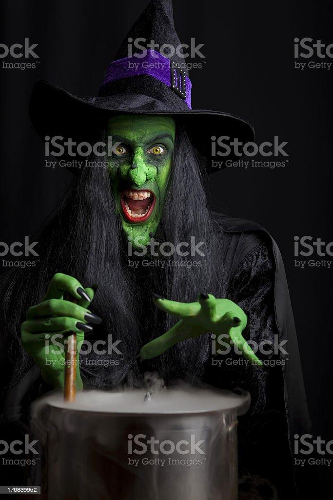 Scary witch stirring a smoky cauldron stock photo