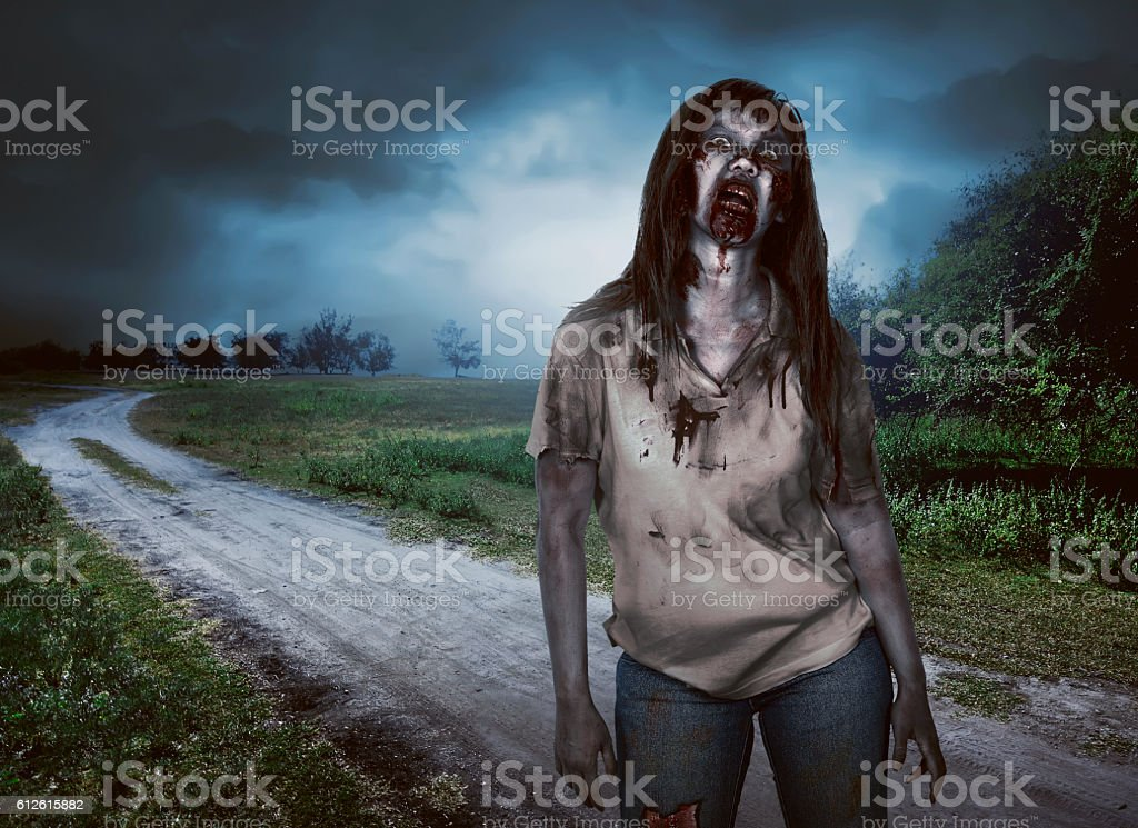 Scary zombie woman with wounds walking stock photo