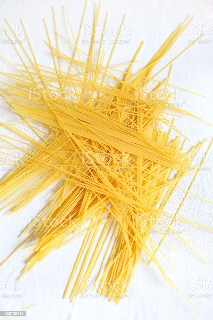 Scattered and messy raw spaghetti pasta . stock photo