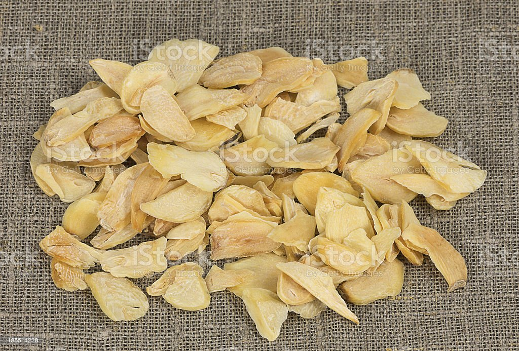 scattered dried garlic on a background of rough cloth royalty-free stock photo
