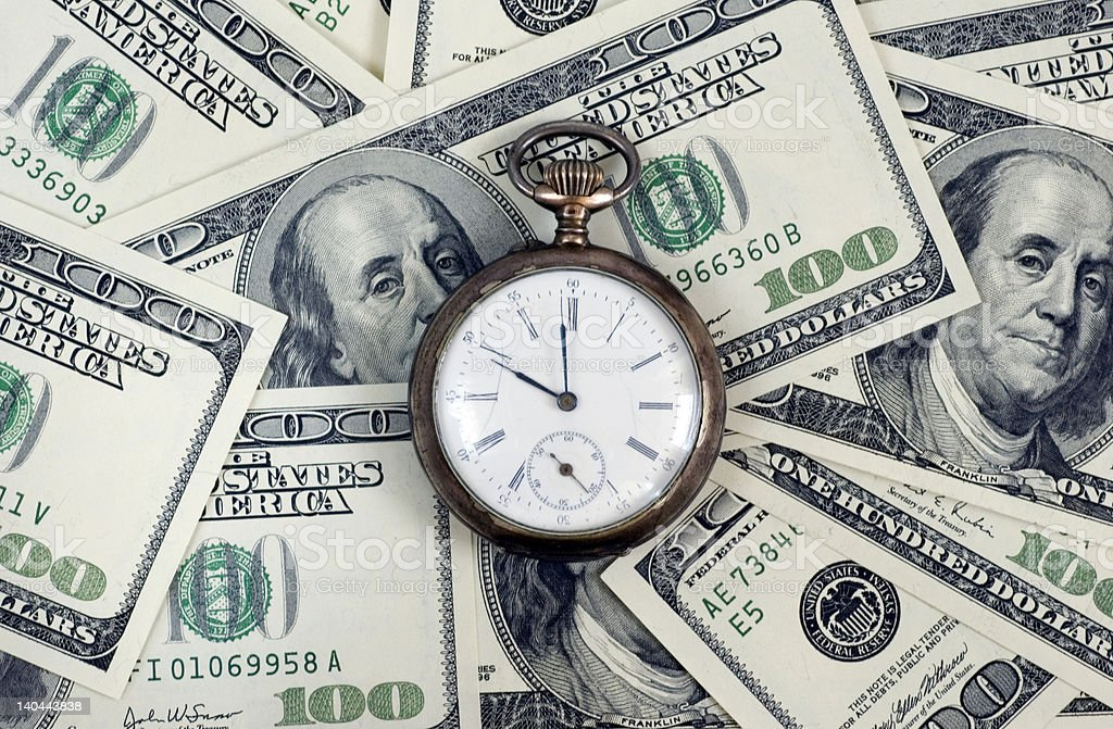 A scattered pile of 100 dollar bills with a pocket watch stock photo