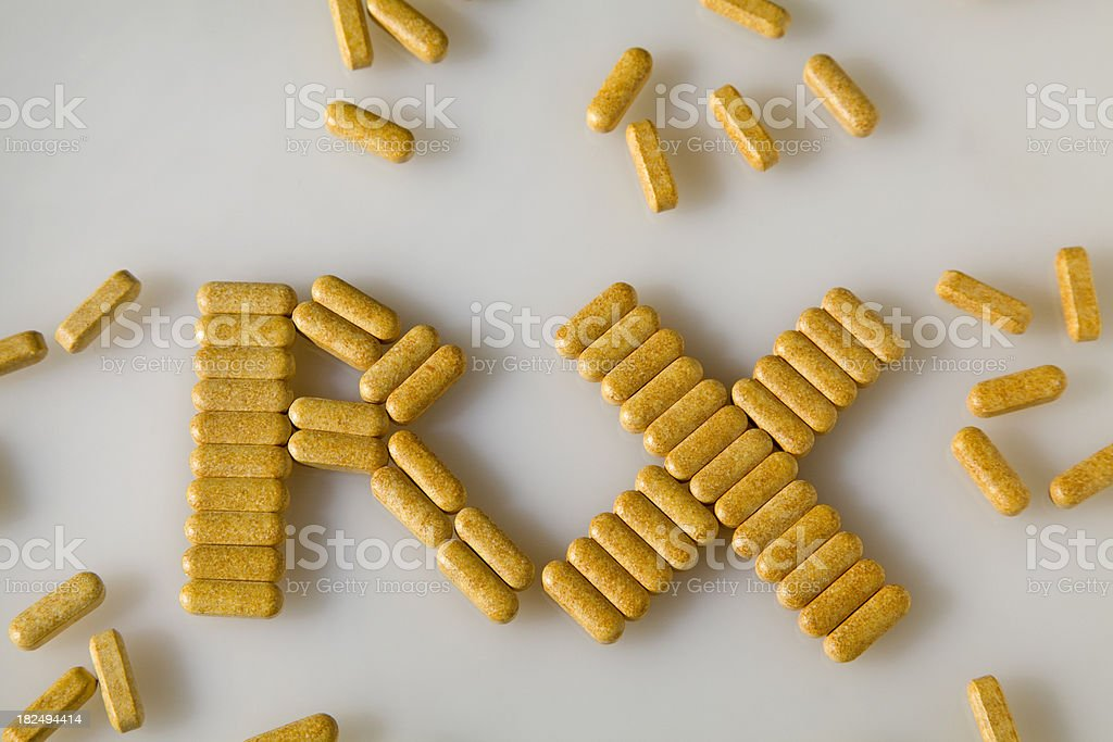 Scattered pills spell out Rx royalty-free stock photo