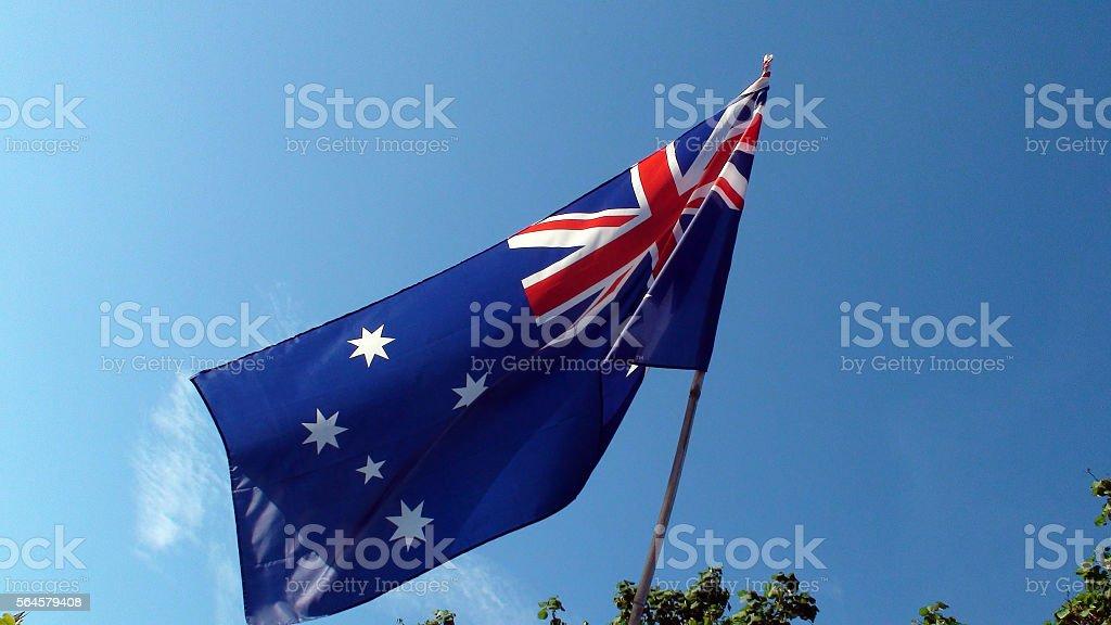 Scene Of Australian Flag Against Clear Blue Sky stock photo