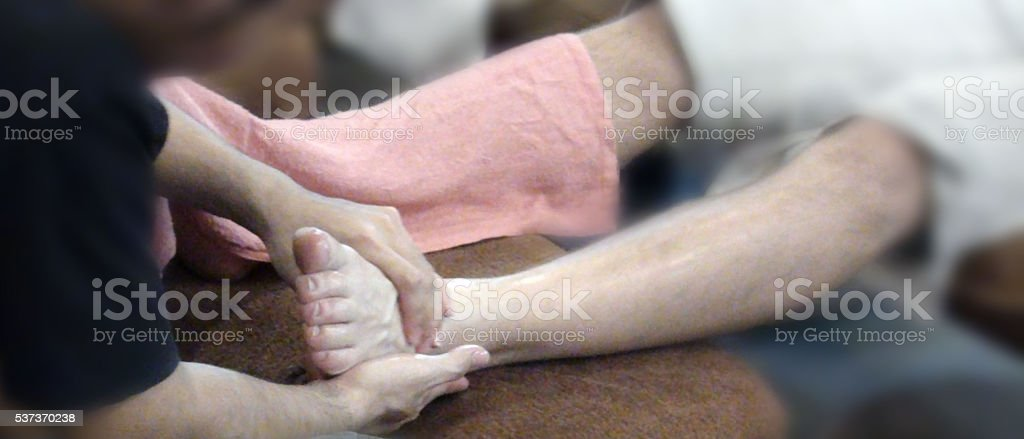 Scene Of Human Hand Massaging Human Foot stock photo