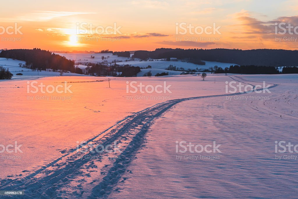 Scene with trail on snow at sunset background stock photo