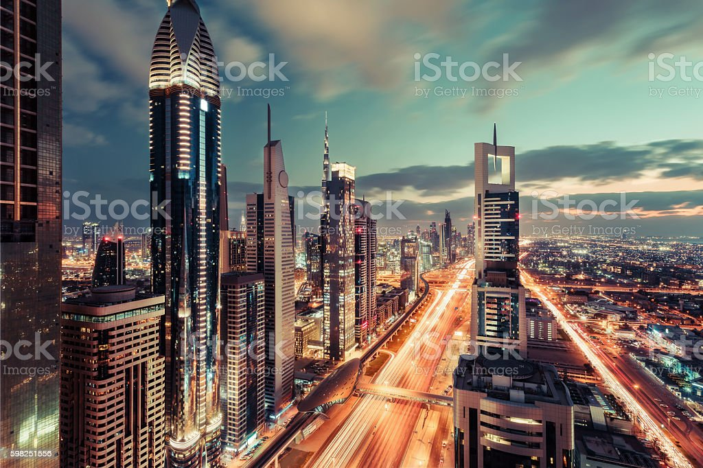 Scenic downtown Dubai skyscrapers at night with illuminated road. stock photo
