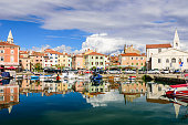 scenic harbour with boats and brightly houses in Izola