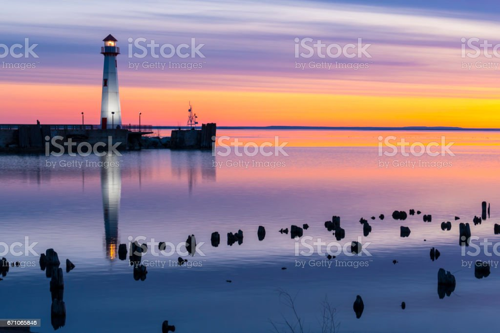 Scenic Lighthouse in calm waters, colorful predawn light. stock photo