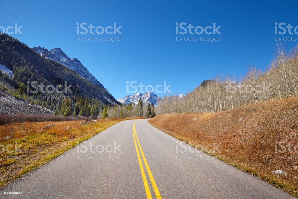 Scenic mountain road, Maroon Bells in distance. stock photo