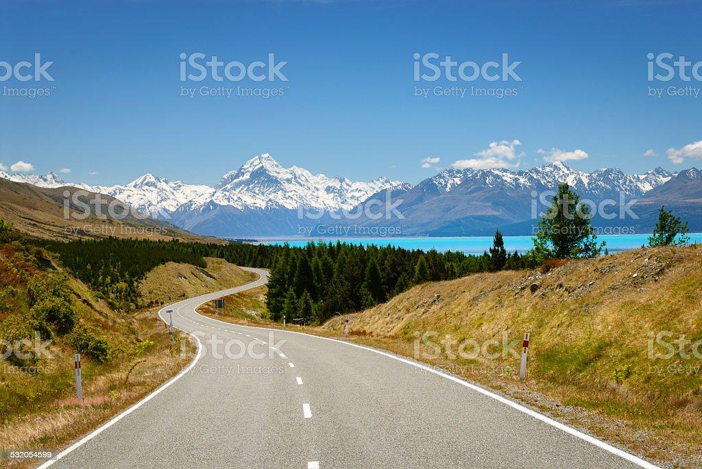 Scenic road winds along glacial blue lake towards mountain range stock photo