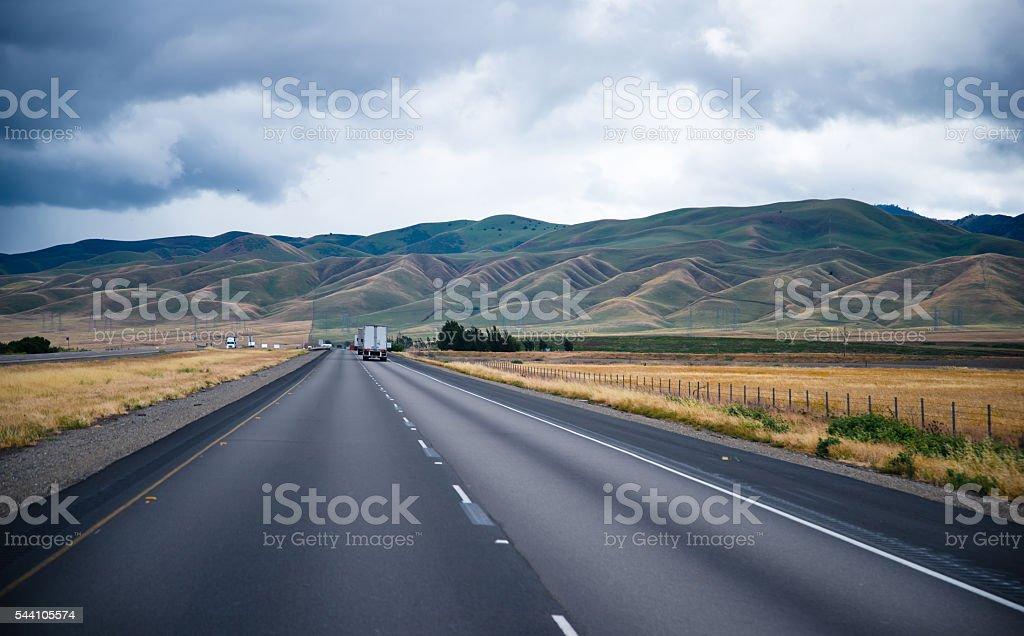 Scenic road with caravans semi trucks and undulating hills stock photo