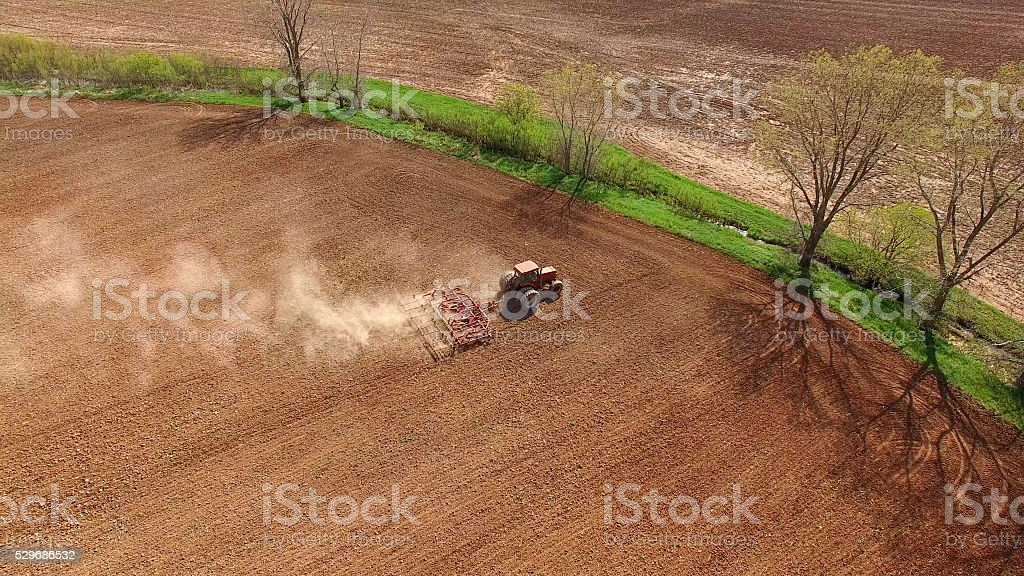 Scenic rural fields being plowed and planted with tractor. stock photo