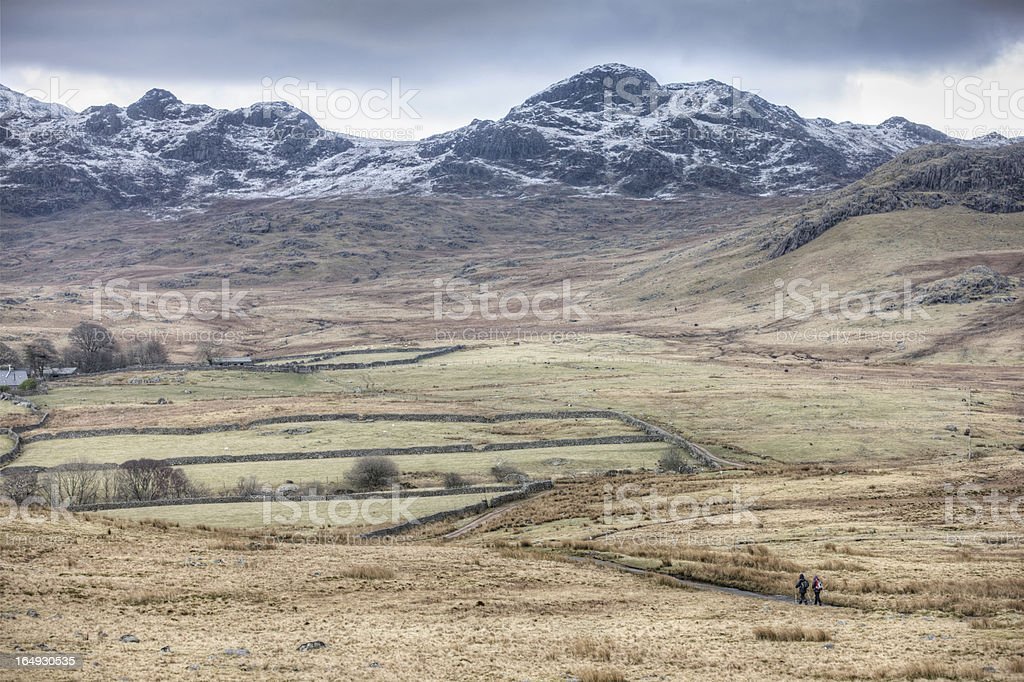 Scenic view across Cumbrian winter moorland two walkers royalty-free stock photo