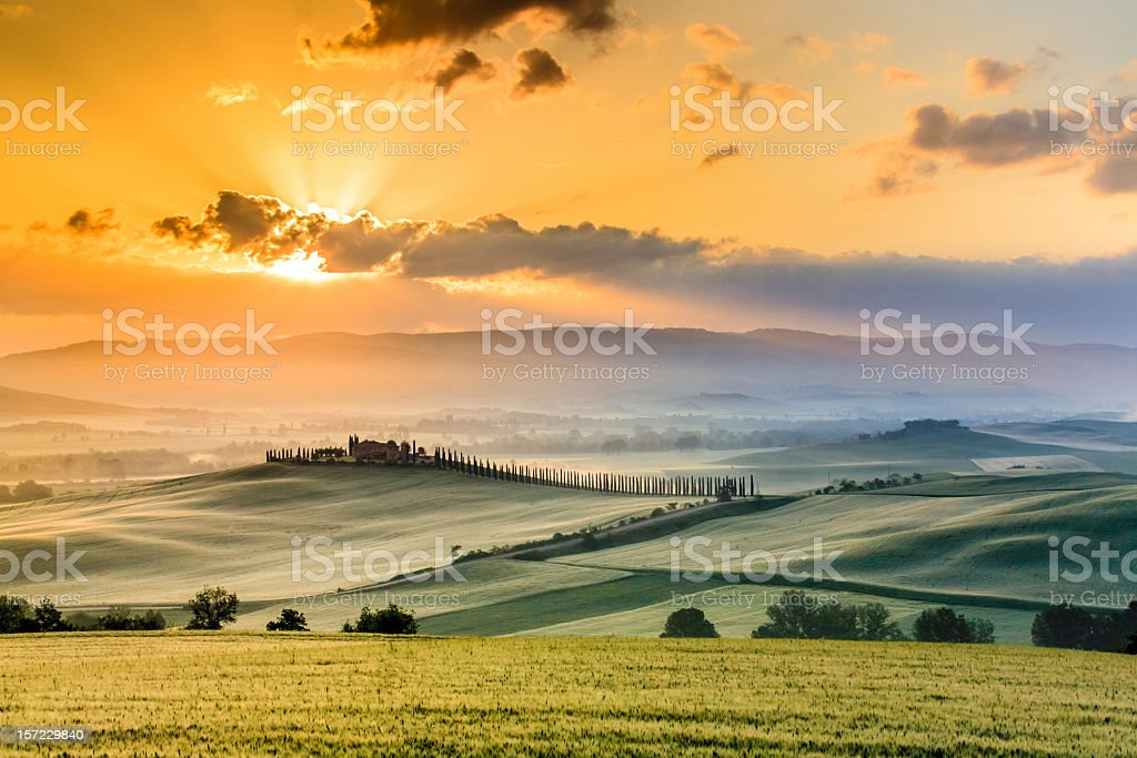 A scenic view of a Tuscany farmhouse in the morning sunrise stock photo