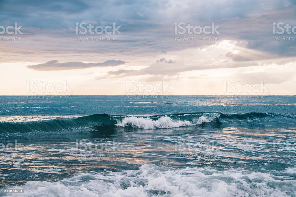 Scenic view of crashing ocean waves under cloudy sky. stock photo