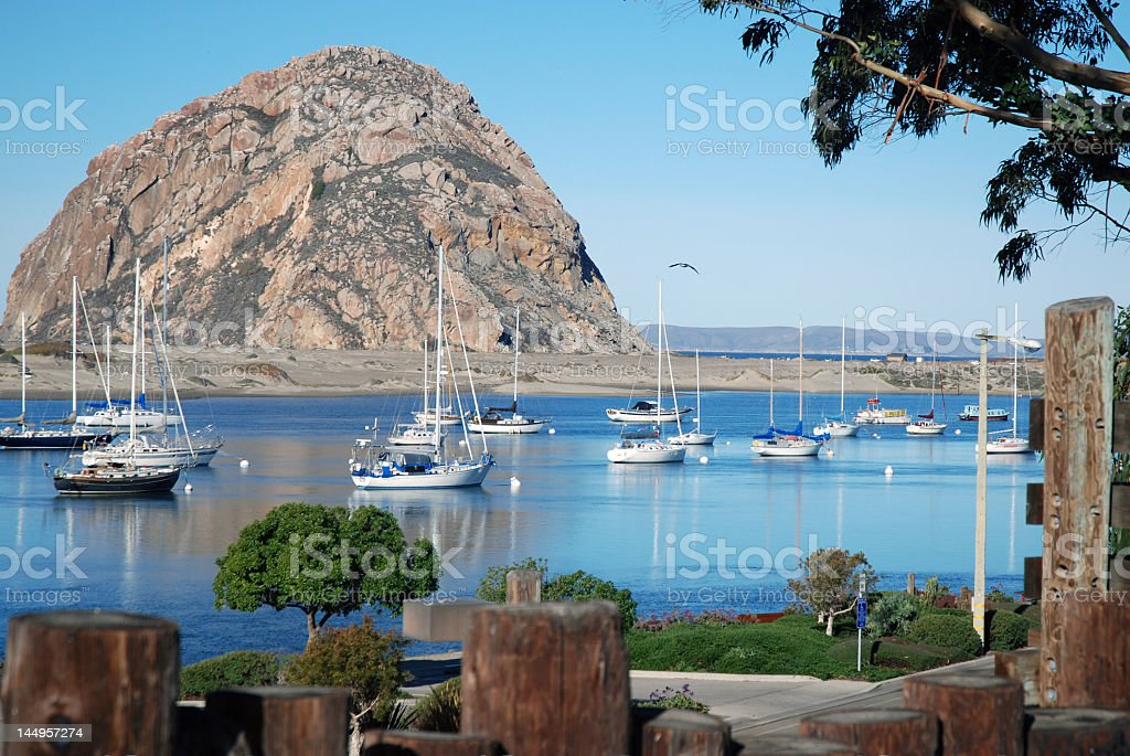 Scenic view of Morro Rock from coastline with boats in water stock photo