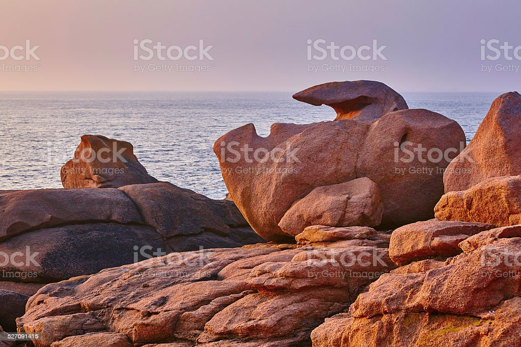 Scenic view of pink granite coast at sunset stock photo