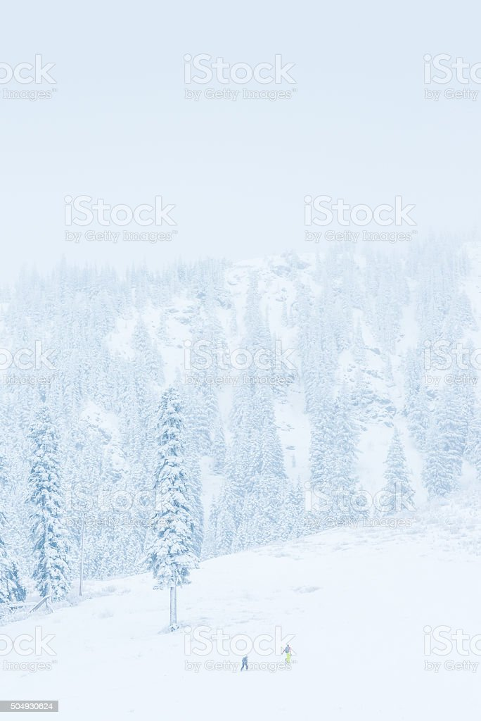 scenic view of small people walking in snow mountain. stock photo