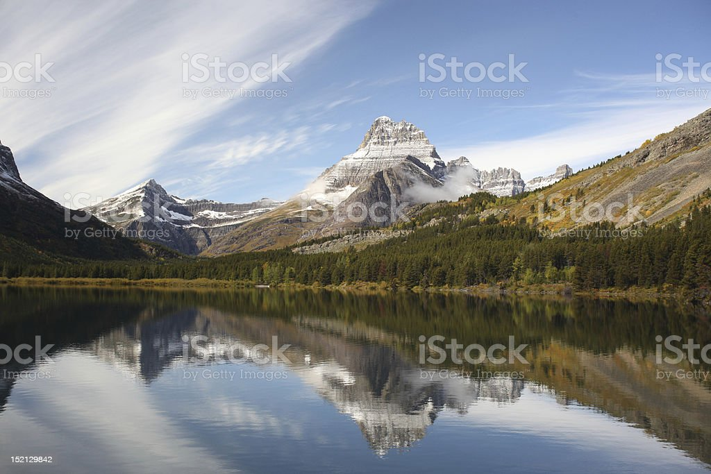 Scenic view of snow capped mountain reflected in lake below stock photo