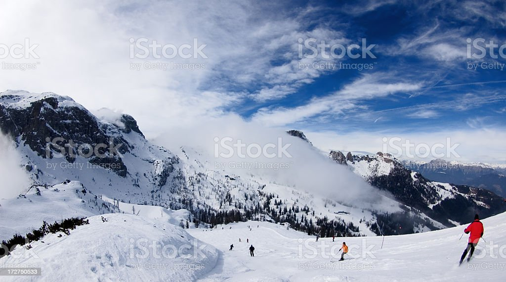 Scenic view of snow capped mountains, skiers and blue sky stock photo
