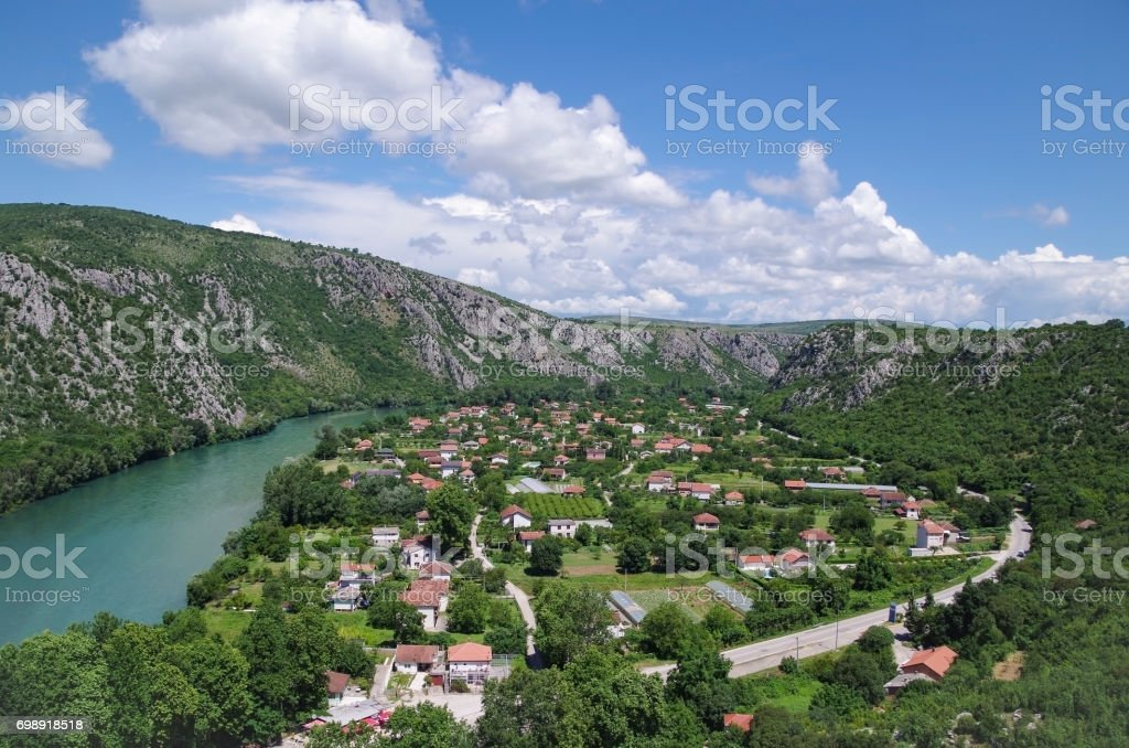 Scenic view of the mountain, valley and the river on a background of colorful blue cloudy sky. stock photo