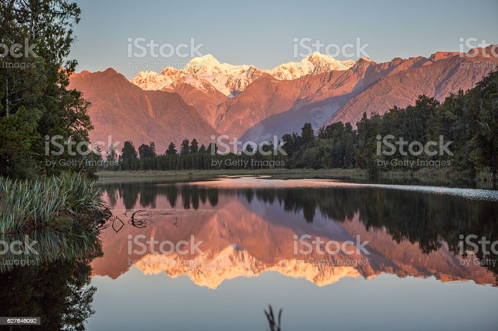 Scenic View Of Trees And Mountains Reflection In Lake Matheson stock photo