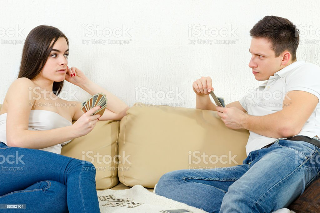 Sceptic young couple cheating each other in card game stock photo