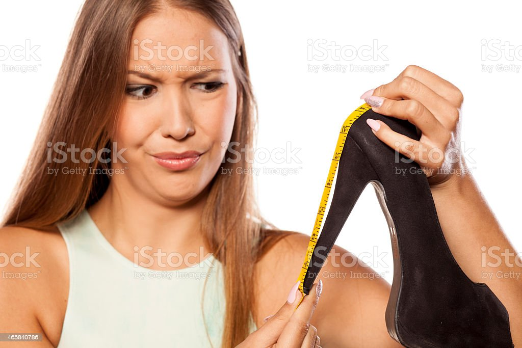 Sceptical young woman measures her heels with a measuring tape stock photo