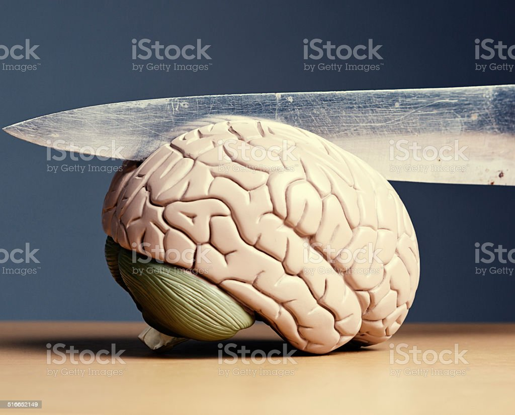Schizophrenia? Knife slicing model brain in half stock photo