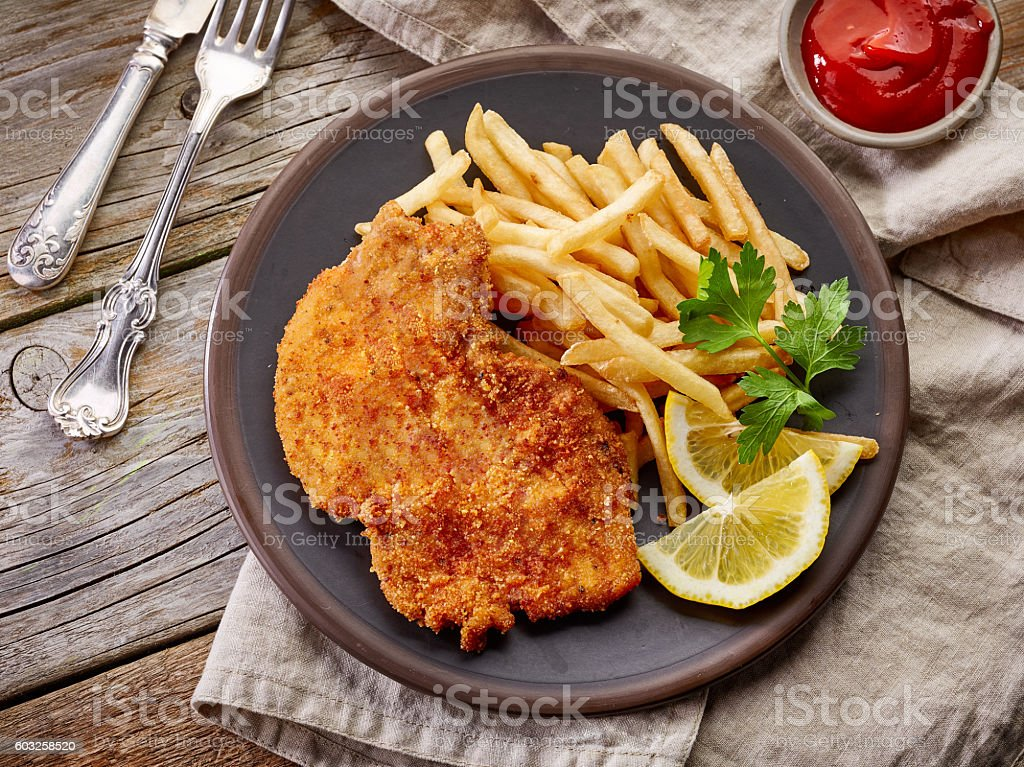 schnitzel and fried potatoes stock photo