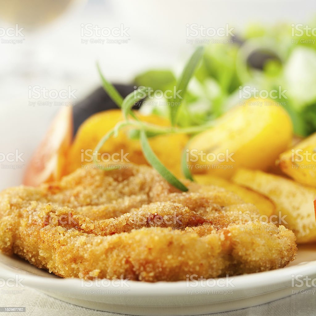 Schnitzel with baked potatoes and herbs royalty-free stock photo
