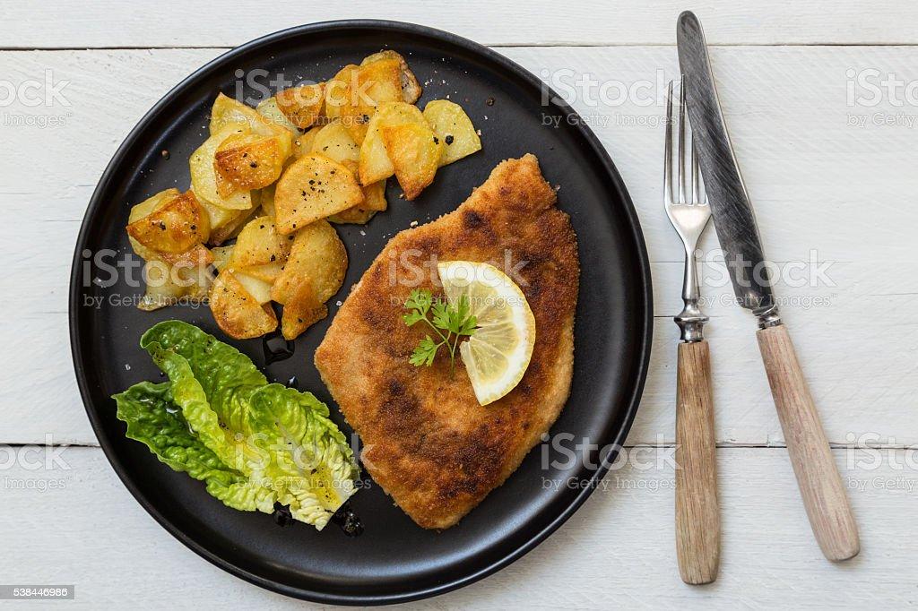 Schnitzel with potatoes salad and lemon stock photo