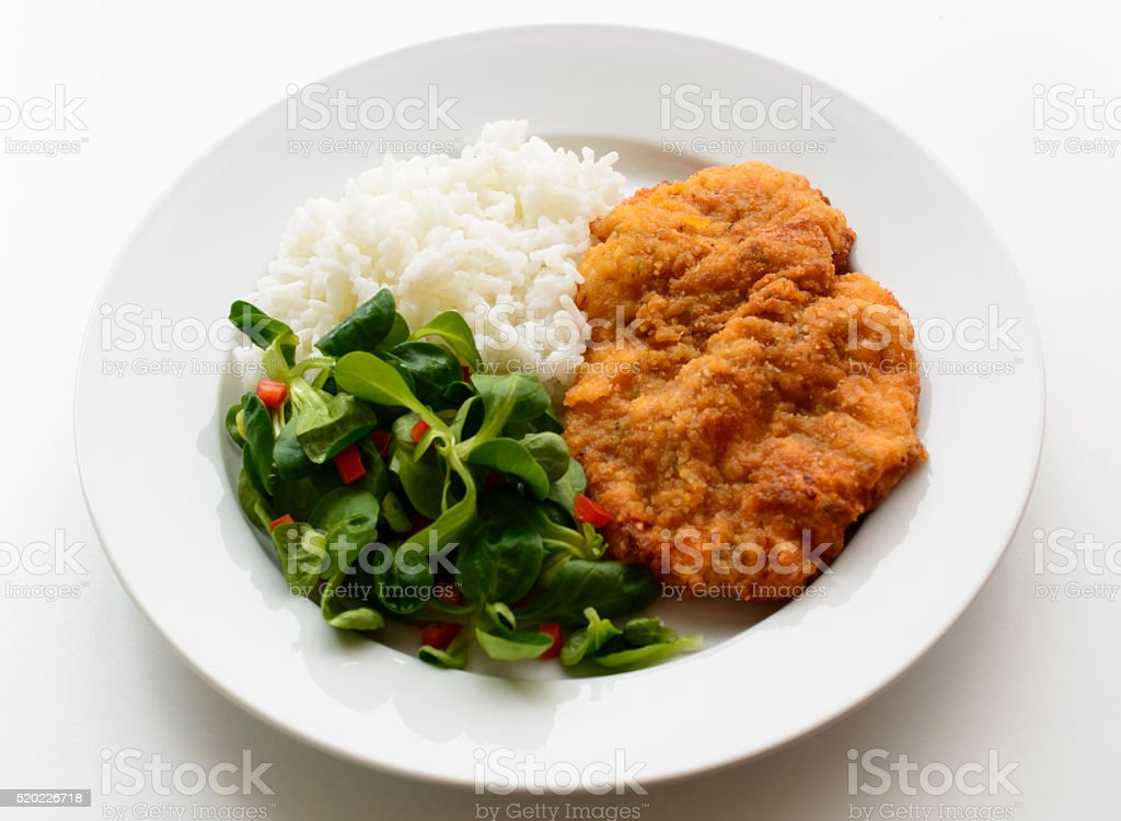 Schnitzel with salad and rice on plate stock photo