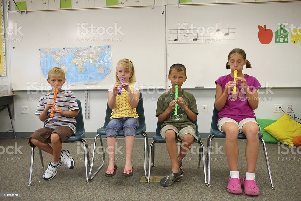 School age children playing colorful recorders in classroom royalty-free stock photo