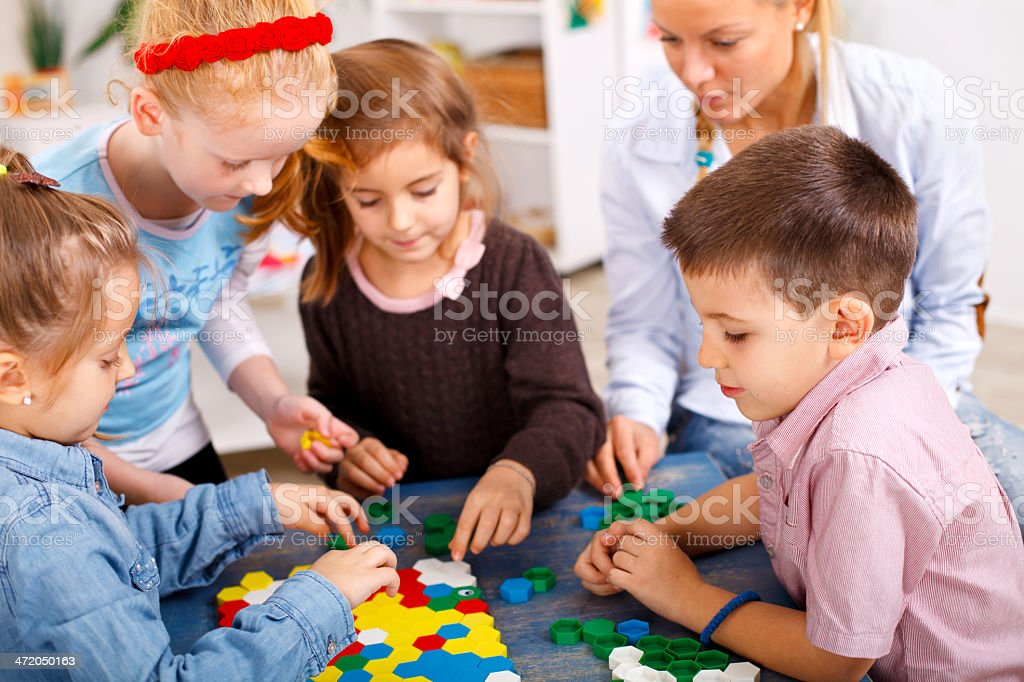 Teacher and children are playing a board game in the classroom