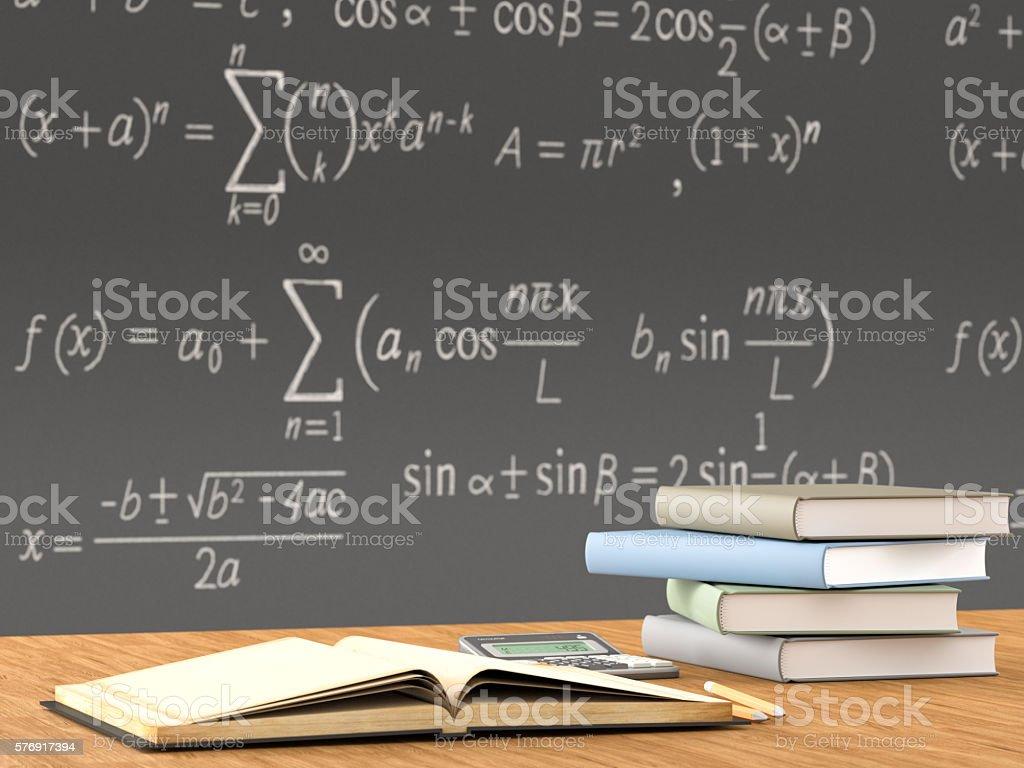 School books on a desk in front of blackboard stock photo