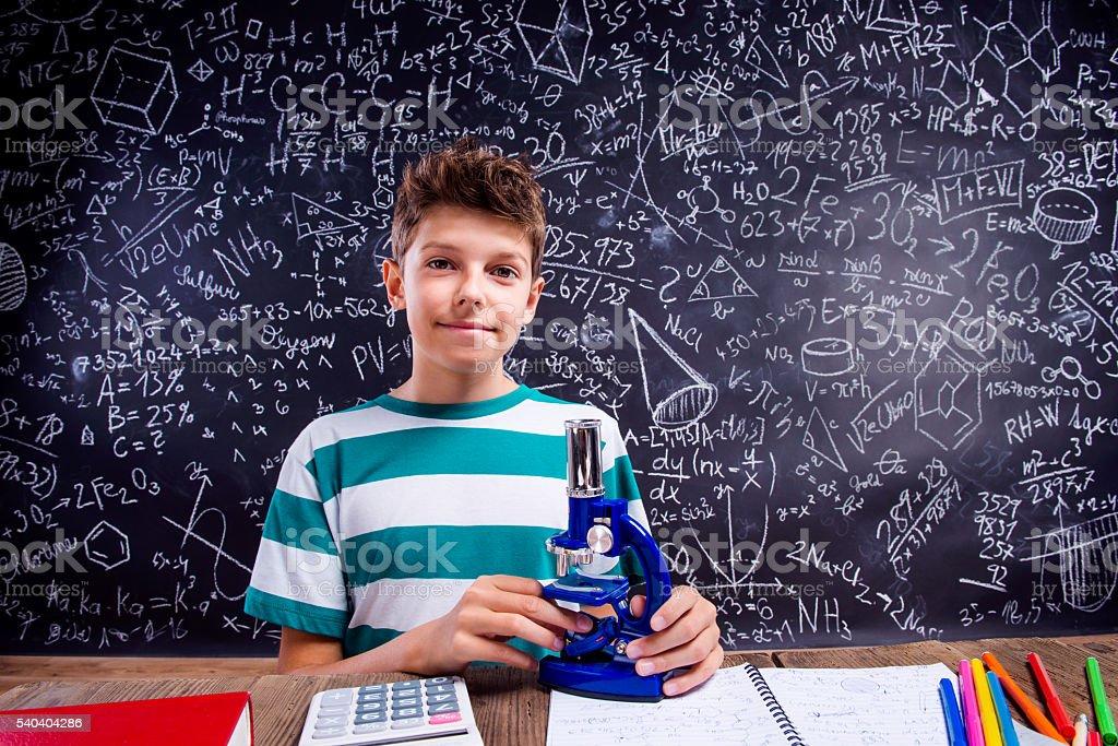 School boy at the desk with microscope, big blackboard stock photo