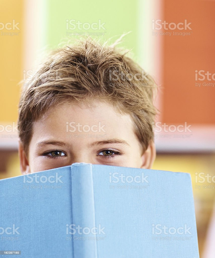 School boy covering his face with a blue book royalty-free stock photo