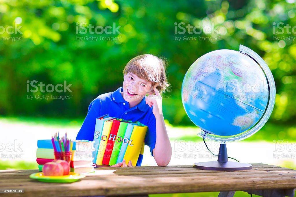 School boy doing homework in school yard stock photo