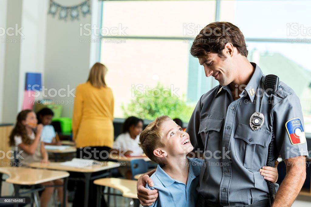 School boy gives policeman a hug stock photo