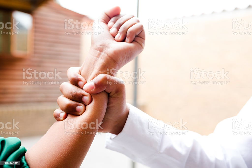 School boy grabs girls arm stock photo