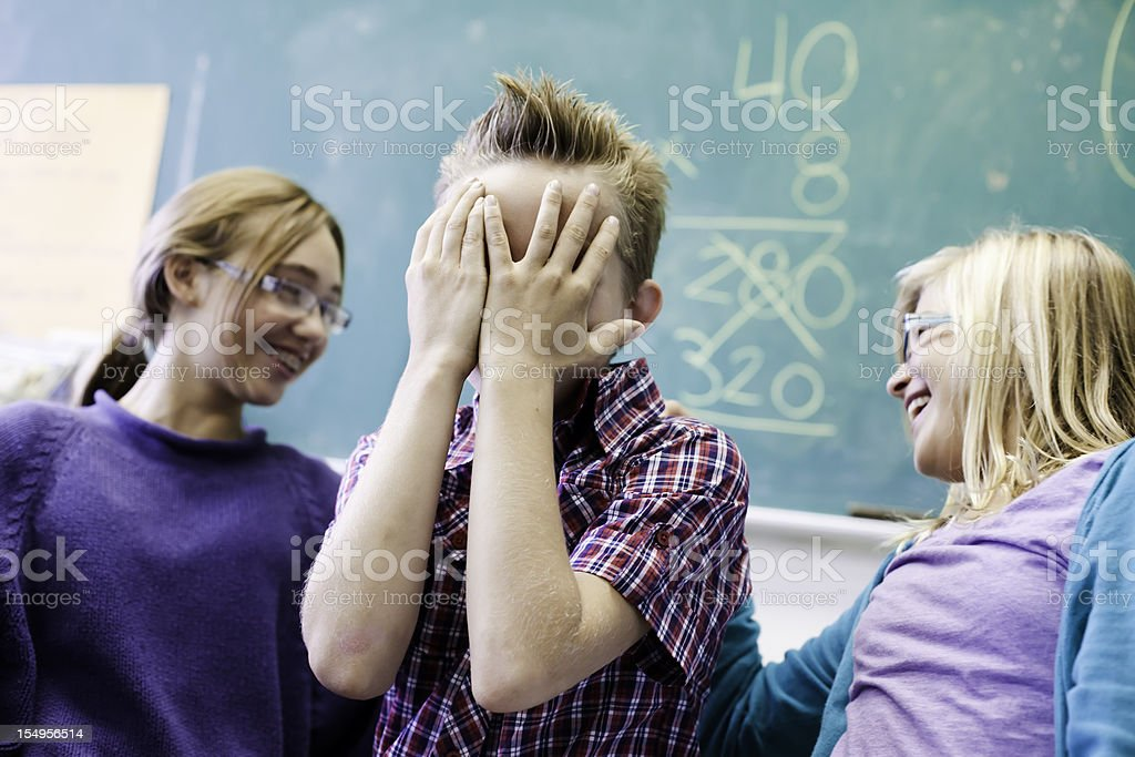School boy hides his face while friends mock him royalty-free stock photo