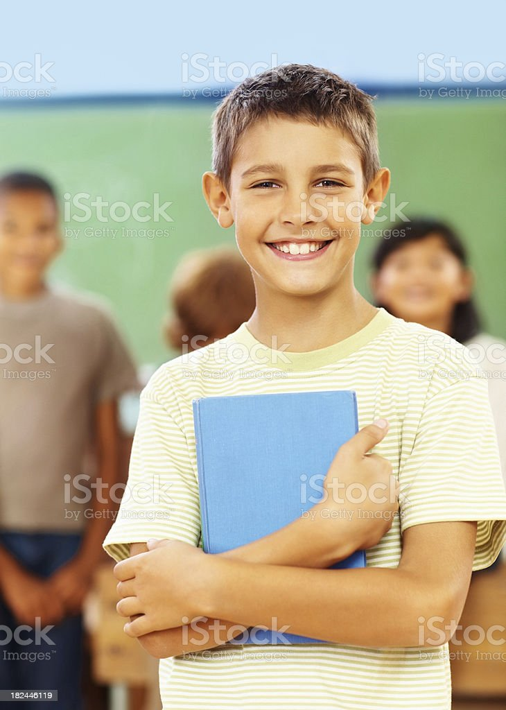 School boy holding a book with classmates at the back royalty-free stock photo